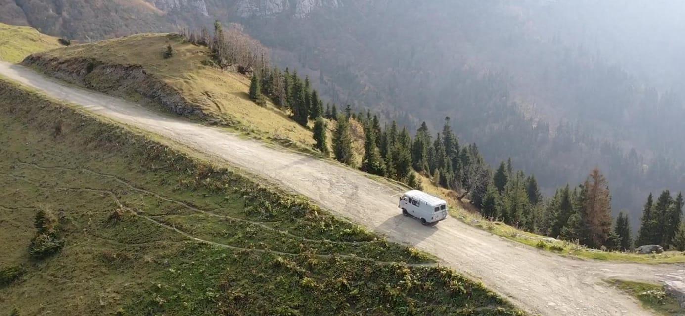 UAZ Buhanka on mountain road drone shot